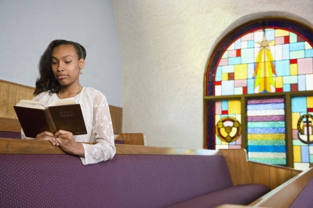African American woman reading Bible in church 스톡 콘텐츠