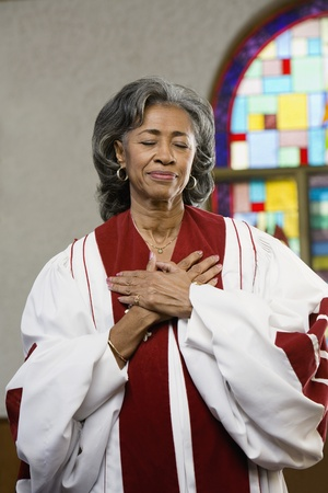 house robe: African American female Reverend with hands on heart
