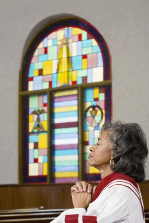 African American female Reverend praying Stock Photo