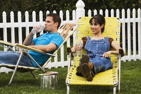 Multi-ethnic couple relaxing in lawn chairs Stock Photo - 16095128