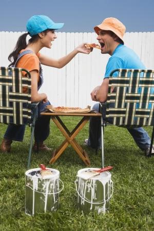 wearying: Multi-ethnic couple eating near newly painted fence