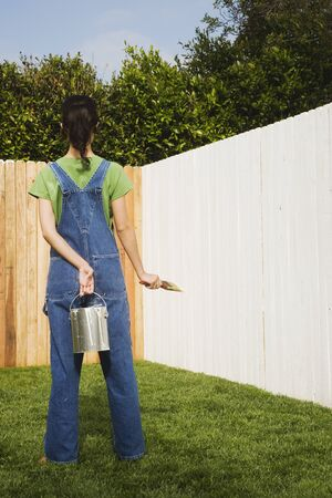 wearying: Hispanic woman painting fence