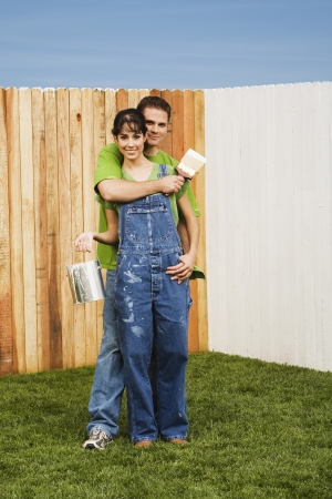 yard work: Multi-ethnic couple painting fence