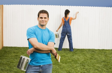 Multi-ethnic couple painting fence Stock Photo - 16095134