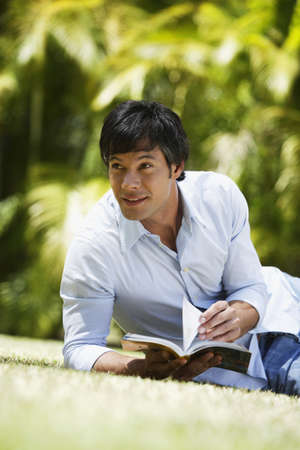 spectating: South American man reading in grass