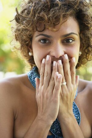 South American woman covering mouth Stock Photo