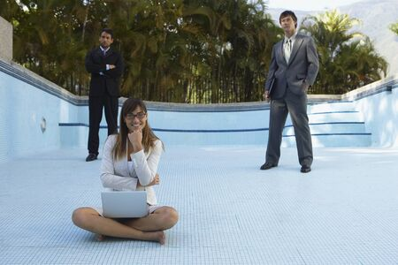 South American businesspeople in empty swimming pool