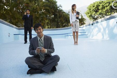 South American businesspeople in empty swimming pool Stock Photo - 16095180