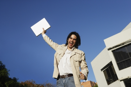 low spirited: South American man holding laptop over head