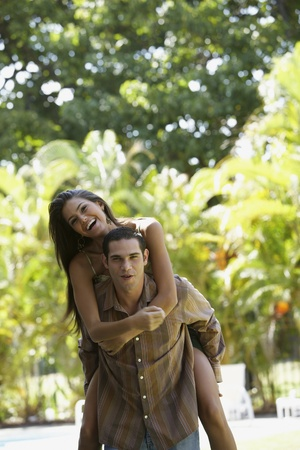 South American man giving girlfriend piggyback ride