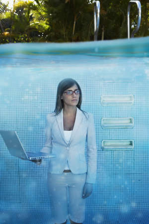 telecommuter: South American businesswoman in swimming pool LANG_EVOIMAGES