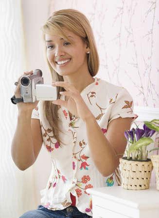 relishing: Hispanic woman holding video camera