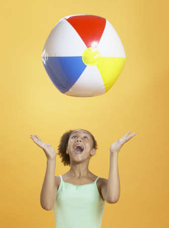 midair: African girl playing with beach ball
