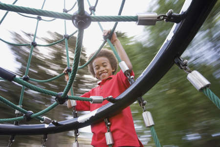 jungle gym: African American boy playing on jungle gym LANG_EVOIMAGES