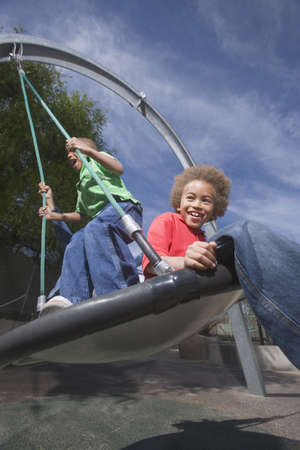 playthings: African American boys playing on swing