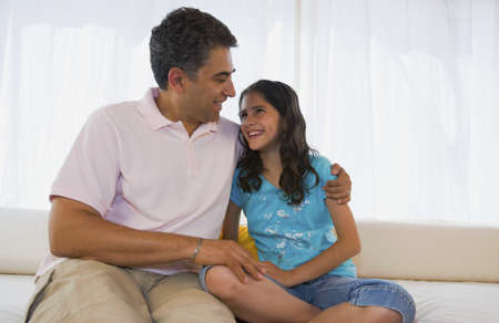 davenport: Hispanic father and daughter smiling at each other LANG_EVOIMAGES