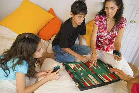 Hispanic family playing board game LANG_EVOIMAGES