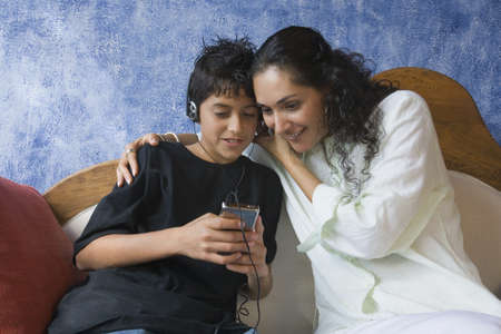 Hispanic mother and son listening to mp3 player Stock Photo - 16095246