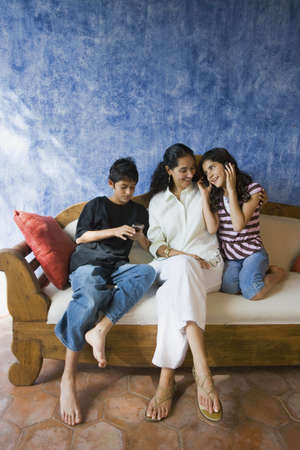 Hispanic mother and children relaxing on sofa Stock Photo - 16095247