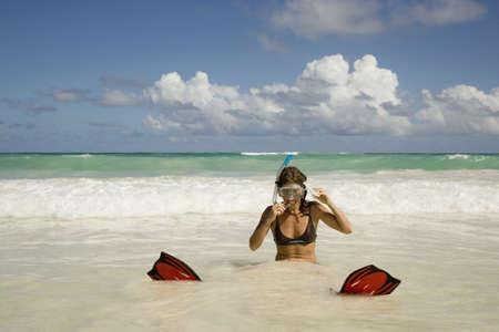 lighthearted: Woman in snorkeling gear sitting in surf