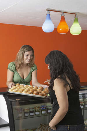 bakery products: Hispanic female business owner in gourmet food store LANG_EVOIMAGES