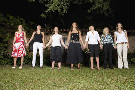 medium group: Hispanic women holding hands in a row LANG_EVOIMAGES