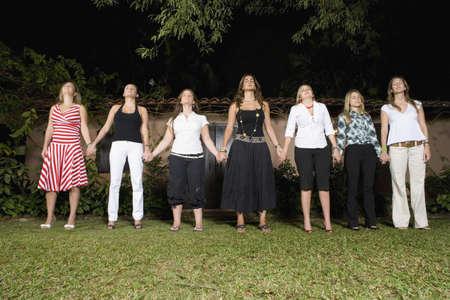 female bonding: Hispanic women holding hands in a row LANG_EVOIMAGES