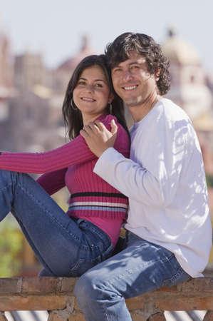 Hispanic couple hugging on railing Stock Photo - 16095316