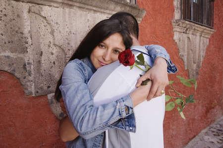 honeymooner: Hispanic couple hugging with rose LANG_EVOIMAGES
