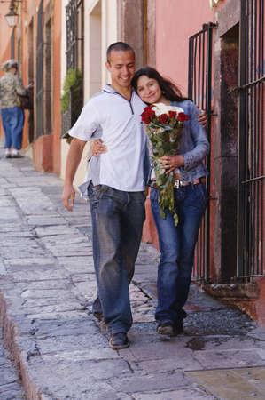 stepping: Hispanic couple on sidewalk with roses
