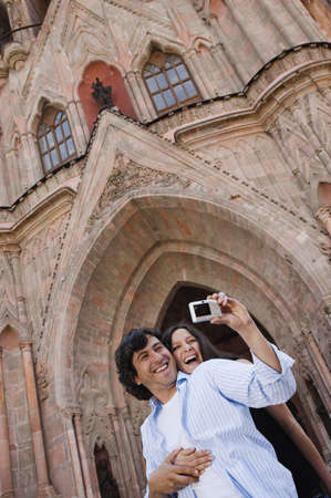 Hispanic couple taking own photograph Stock Photo - 16095326
