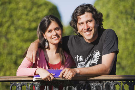 leaning by barrier: Hispanic couple leaning in railing LANG_EVOIMAGES