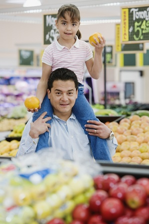 citrus family: Hispanic father and daughter in produce department LANG_EVOIMAGES