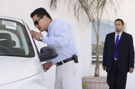 Hispanic man looking at new car Stock Photo - 16095377