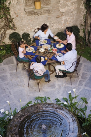 Hispanic family eating at outdoor restaurant Foto de archivo