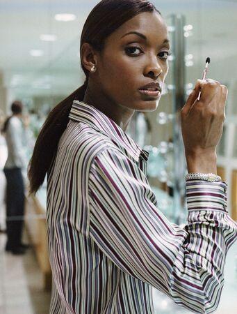 African American woman applying makeup Stock Photo - 16095405