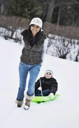 Asian women pulling child on sled Stock Photo - 16095424