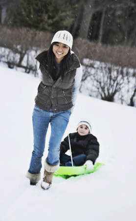 Asian women pulling child on sled Stock Photo - 16095424