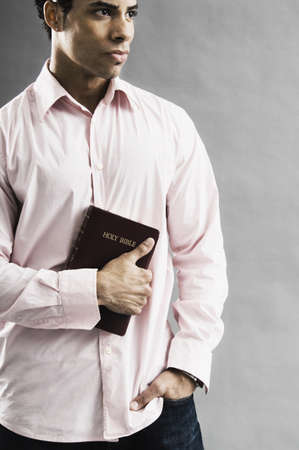 one mid adult man only: Mixed Race man holding the bible