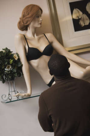 spectating: African man looking at lingerie mannequin LANG_EVOIMAGES