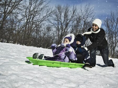 Mother pushing children on sled Stock Photo - 16095442