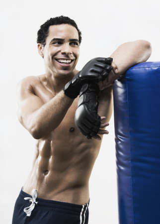 Mixed Race man leaning on punching bag Stock Photo - 16095446