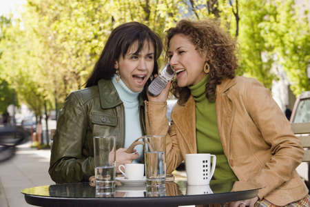 coffee table: Hispanic women talking on cell phone LANG_EVOIMAGES