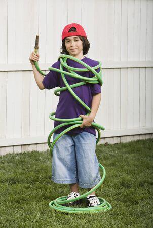 Mixed Race boy wrapped in garden hose