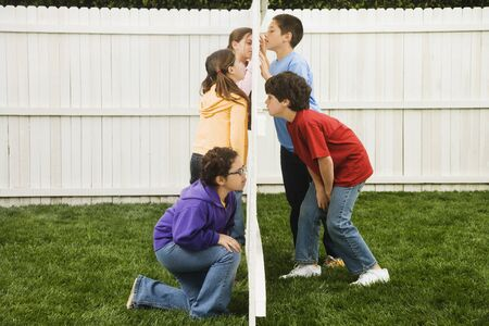 snooping: Mixed Race children looking at each other through fence LANG_EVOIMAGES