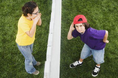 Mixed Race girl yelling to boy through fence Stock Photo - 16095486