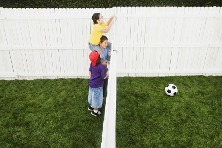 Mixed Race children looking over fence at soccer ball Stock Photo - 16095487