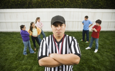 Hispanic referee between groups of girls and boys Stock Photo - 16095490