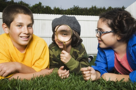 Mixed Race children playing with magnifying glass