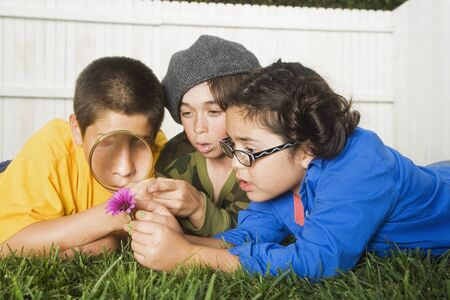 Mixed Race children playing with magnifying glass Stock Photo - 16095496